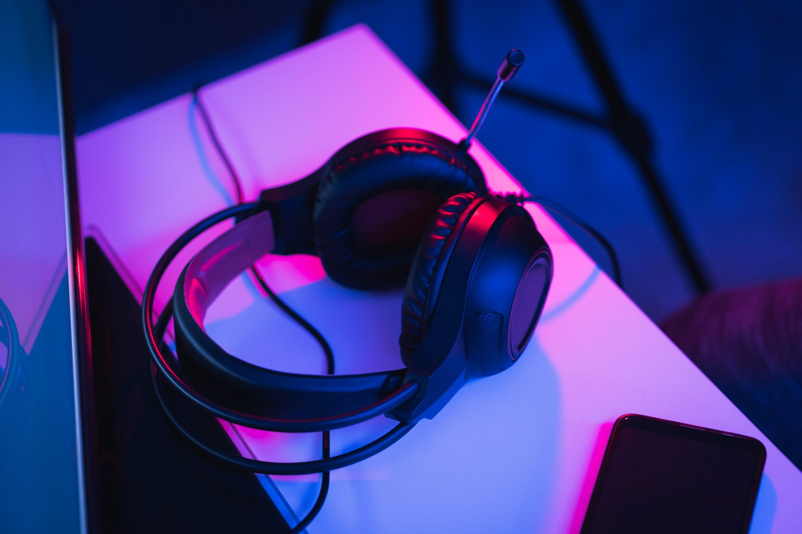 Auriculares sony de PS4 negros sobre una mesa con luz morada