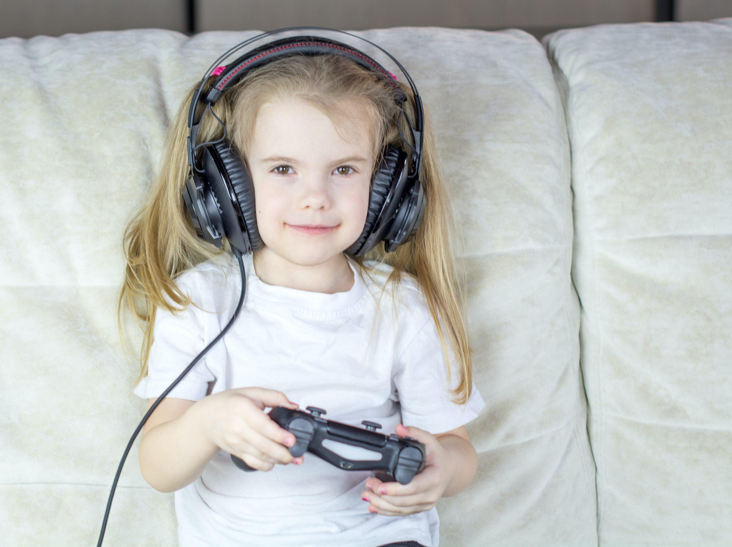 Niña usando auriculares y mando de PS4