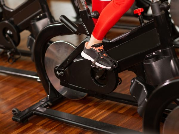 Attractive woman in a red sports suit in gym, riding on speed stationary bike. Women's legs close up.