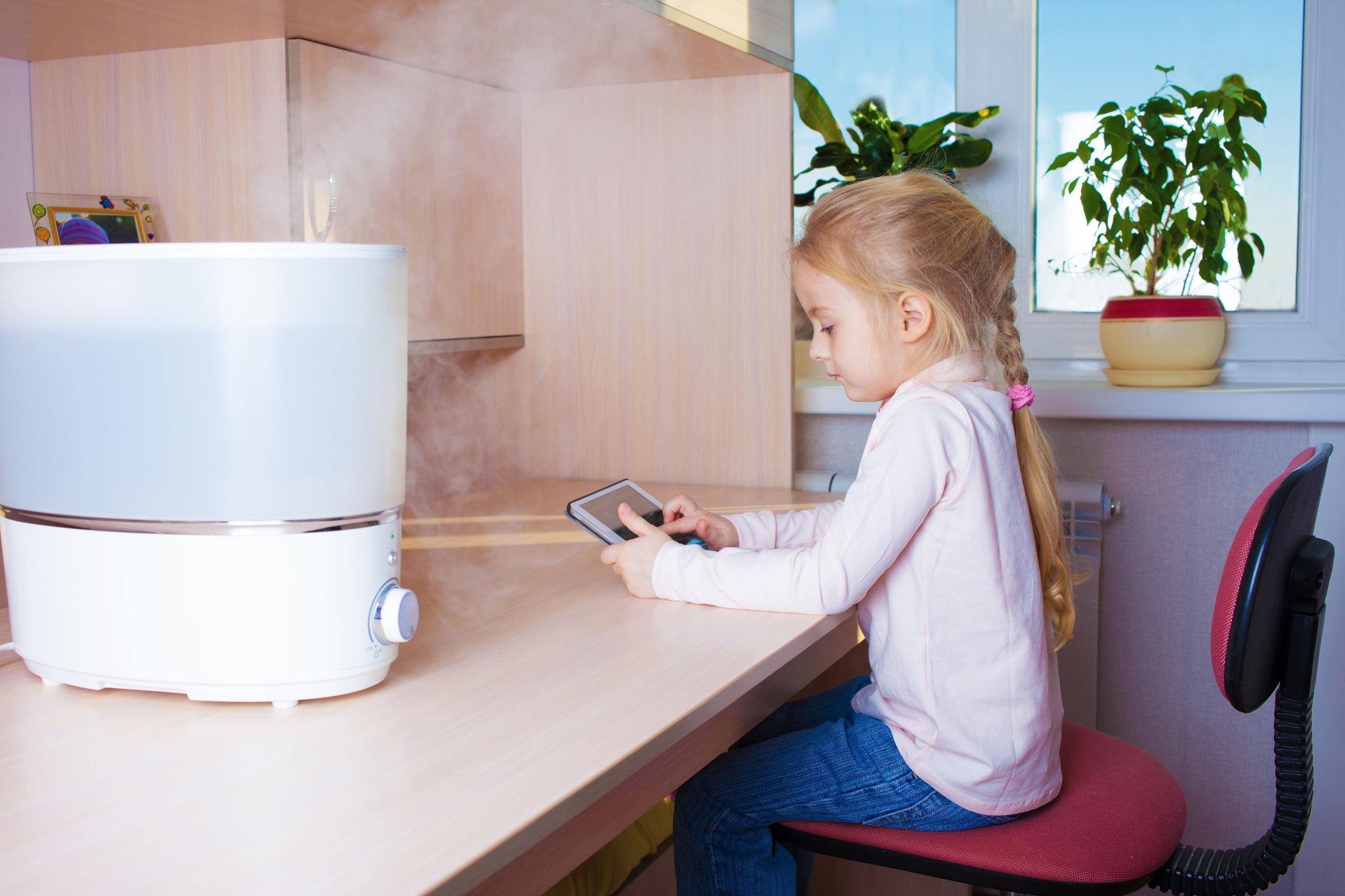 Niña con tablet pc sentada en la mesa cerca del humidificador