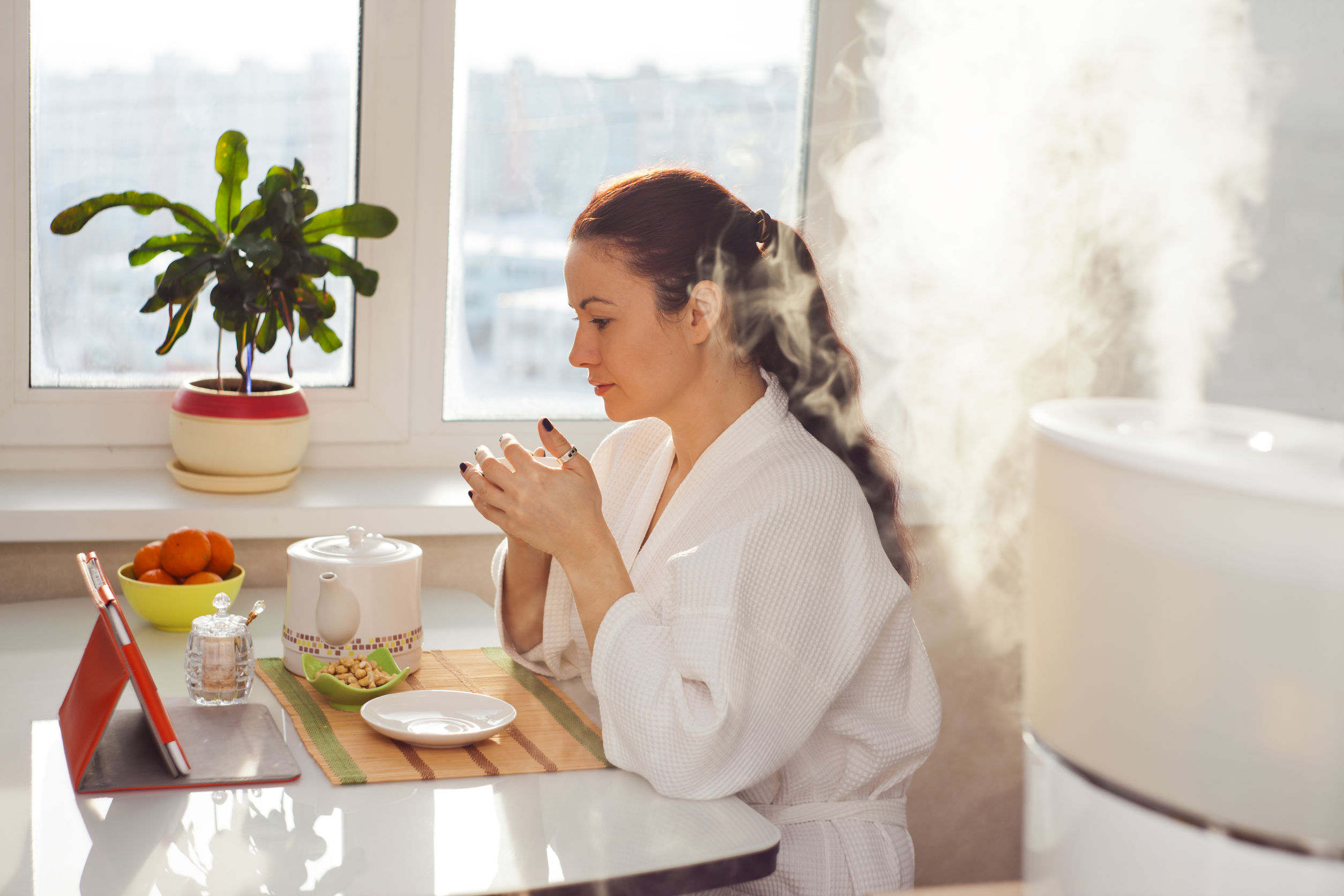 Mujer bebiendo té leyendo tableta cerca del climatizador