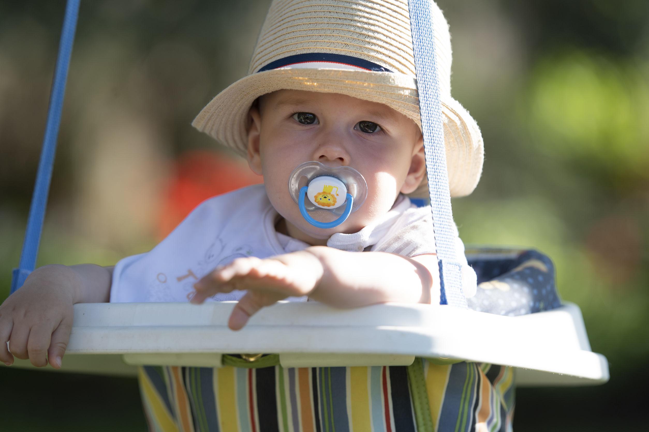 Un bebé con un sombrero de paja se balancea en un patio de recreo al aire libre.