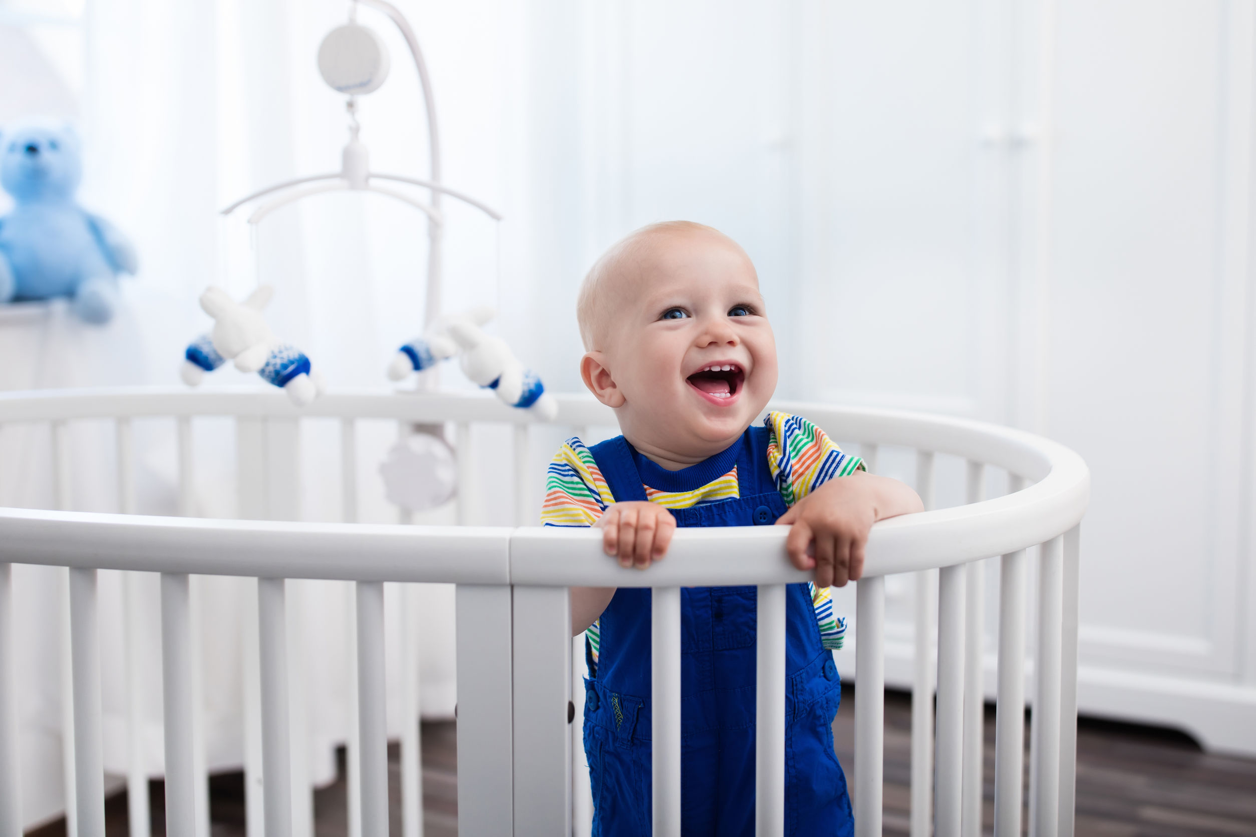 Bebé de risa linda que se coloca en una cama redonda blanca.