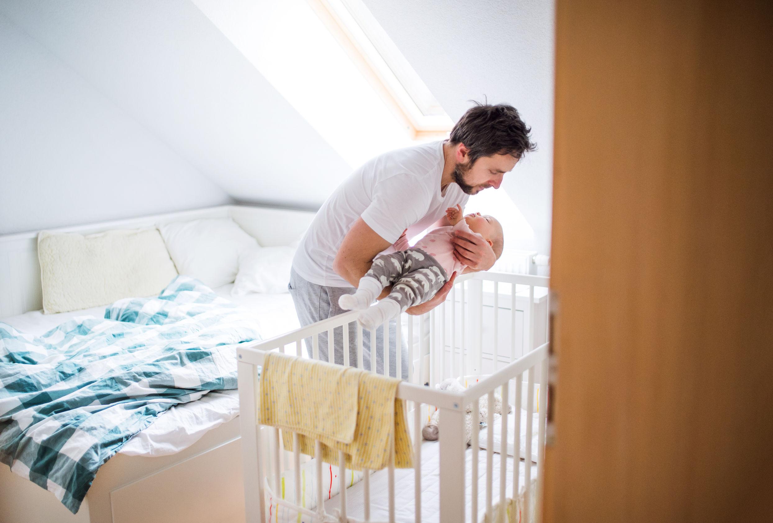 Padre maduro poniendo a una niña pequeña durmiendo en una cuna en casa.