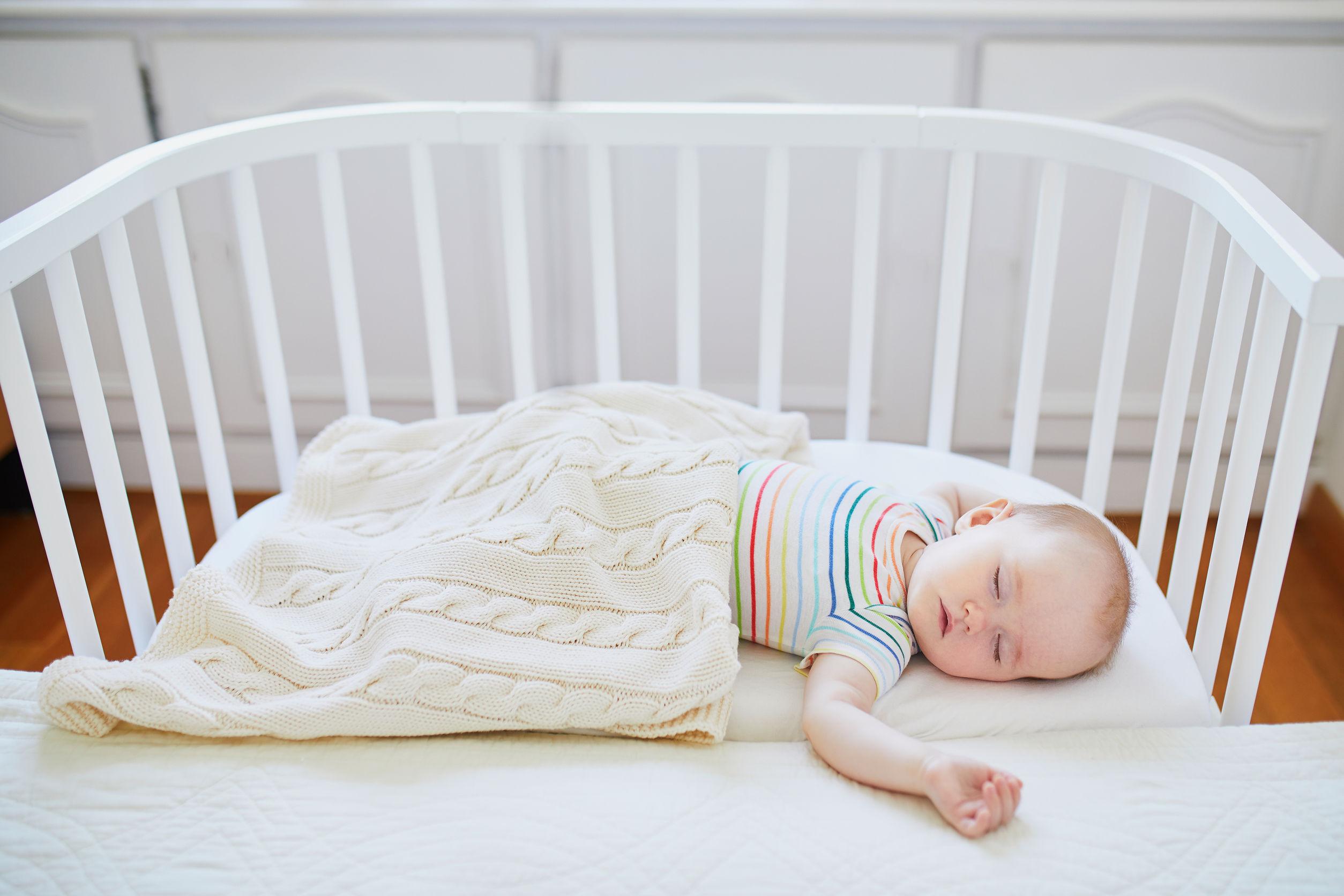 Adorable niña durmiendo en una cuna para dormir junto a la cama de los padres.