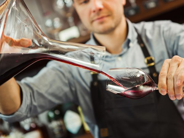 Sommelier pouring wine into glass from decanter. Male waiter pour out alcohol beverage into wineglass at bar counter. Bartender at work