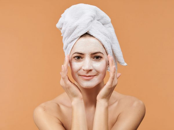 Young woman with white bath towel in her hair and mouisturizing face mask. Wellness and Spa concept on beige background.