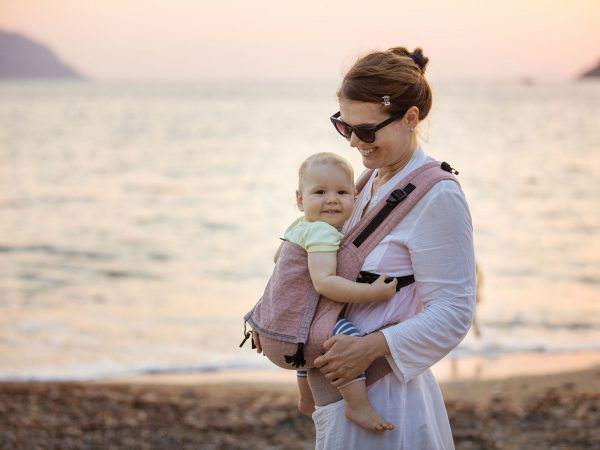 Cheerful Caucasian woman with baby daughter in buckle carrier on beach at sunset