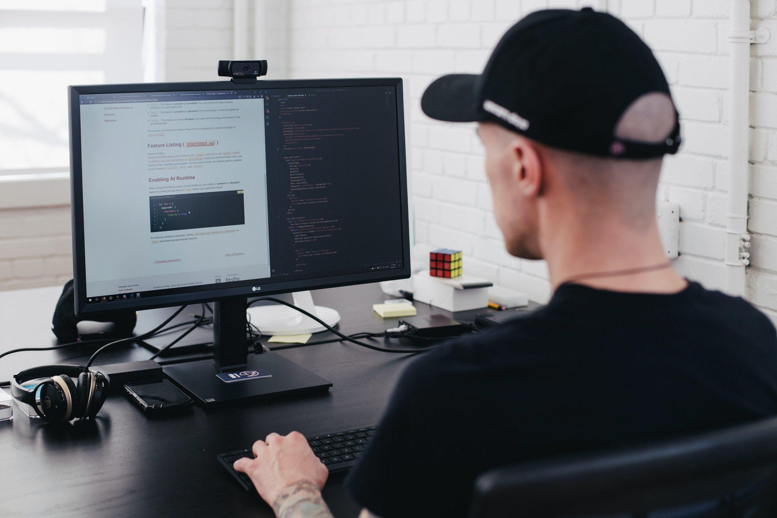 Hombre trabajando en computadora con monitor HP