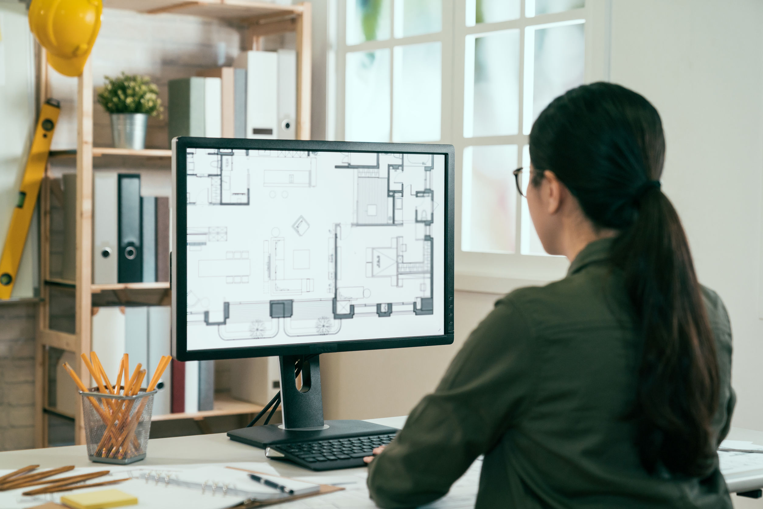 Diseñadora de interiores femenino trabajando monitor de computadora de escritorio escribiendo teclado