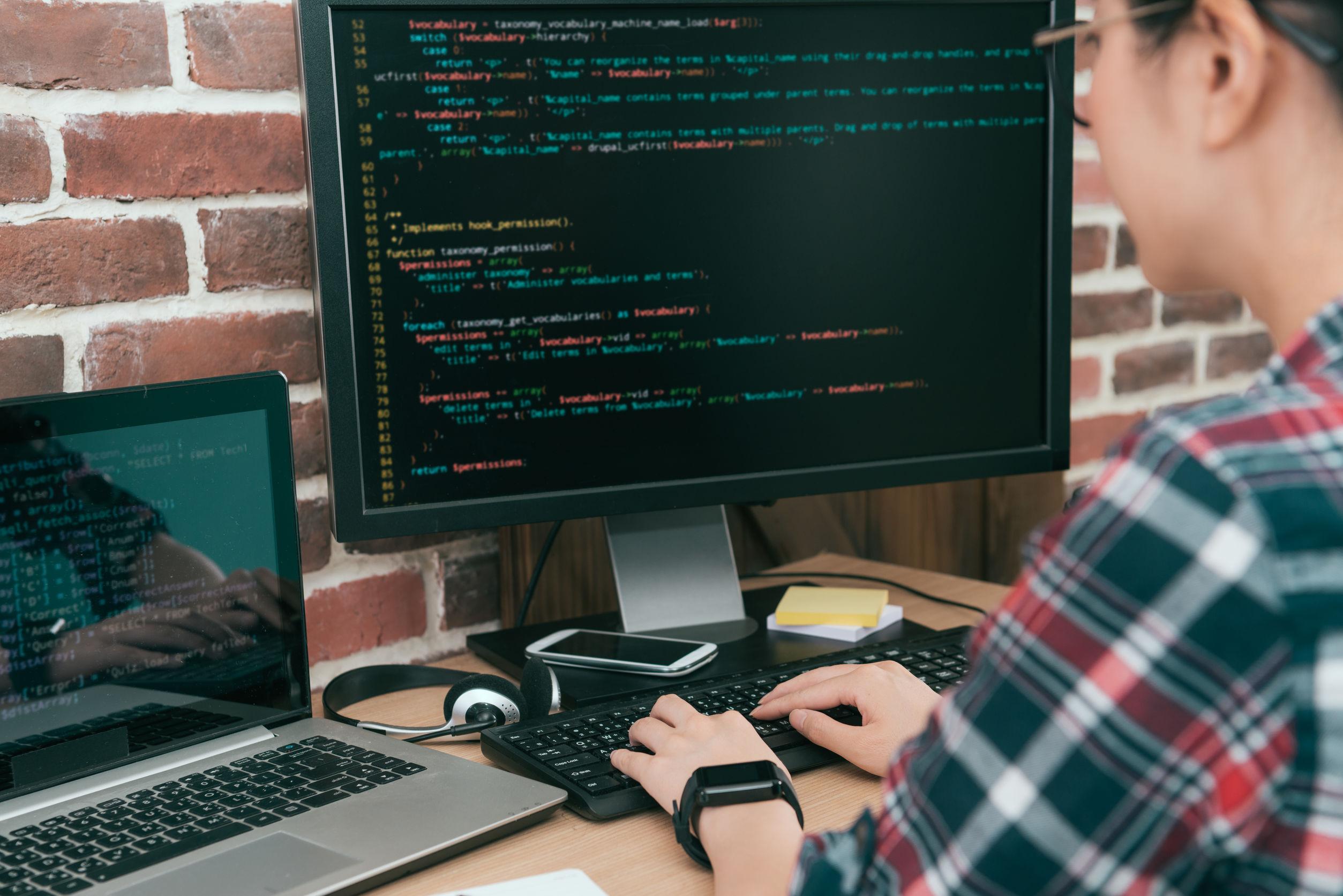 Mujer programadora trabajando en PC y laptop
