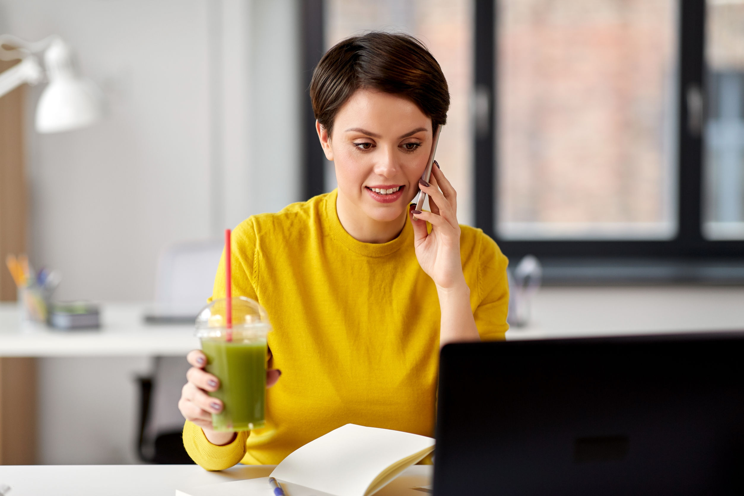mujer con batido y portátil llamando al teléfono inteligente en la oficina