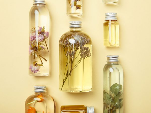top view of transparent bottles with natural beauty products and dried wildflowers on yellow background