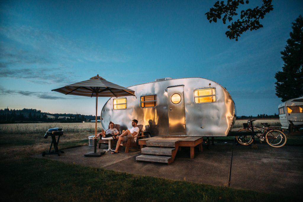pareja acampando con casa rodante