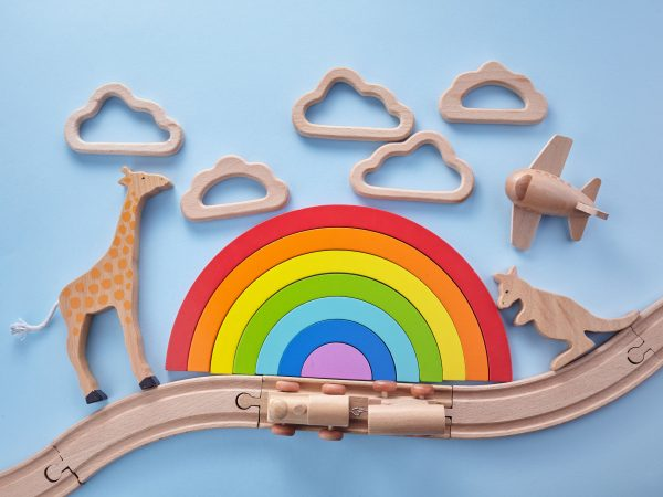 Colorful wooden toys background with rainbow. Preschool and childhood. Zero waste concept.