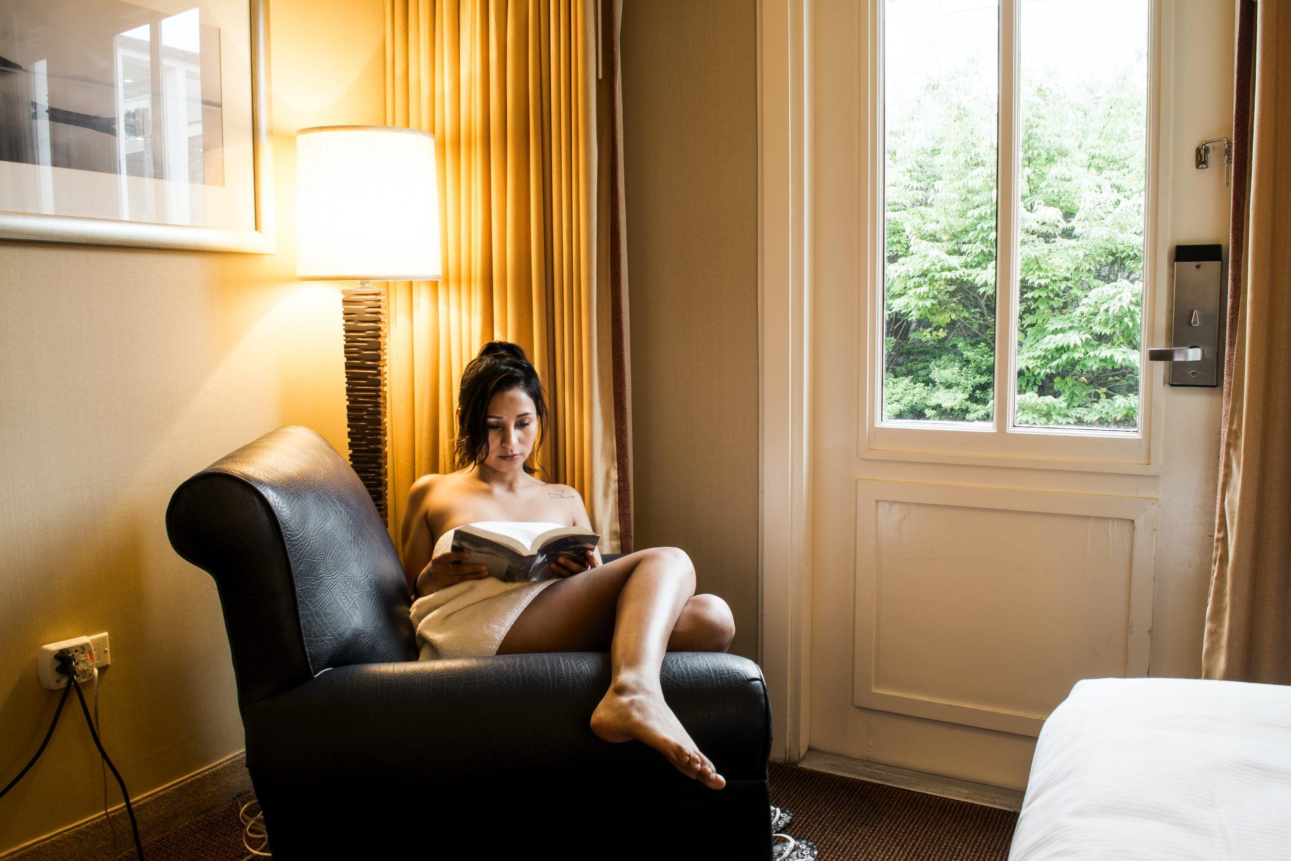chica leyendo al lado de lampara