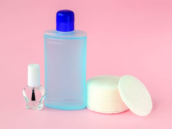 Glass bottle with colorless nail polish, plastic bottle with nail varnish remover and cotton pads on a pastel pink background. Manicure, pedicure, nail care products. Front view.
