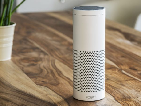 MUENSTER – JANUARY 27, 2018: White Amazon Echo Plus, Alexa Voice Service activated recognition system photographed on wooden table in living room, Packshot showing Amazon Logo