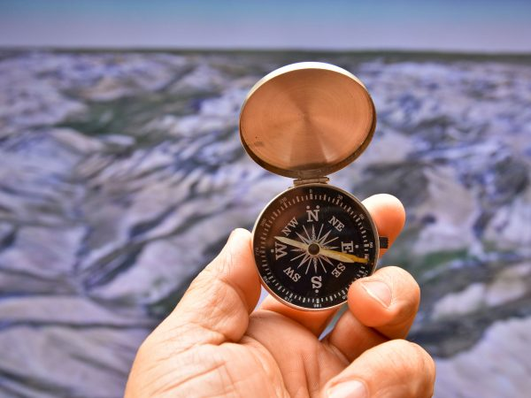 Compass in hand on background of the relief. Man's hand holds a magnetic compass.