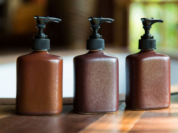 beauty, spa, luxury and bodycare concept – set of bottles with liquid soap or body lotion set at hotel spa bathroom