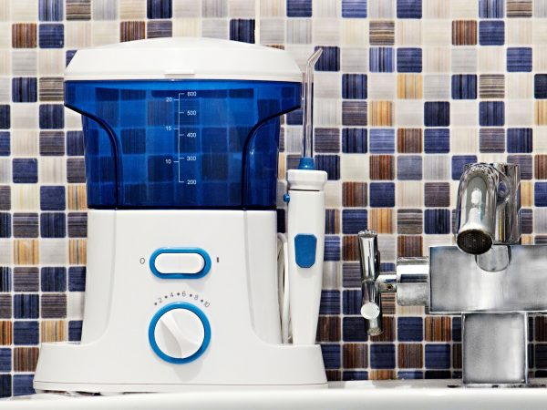Oral hygiene, bathroom objects concept. Mouth teeth cleaning irrigator modern tool on sink. white and blue teeth irrigator