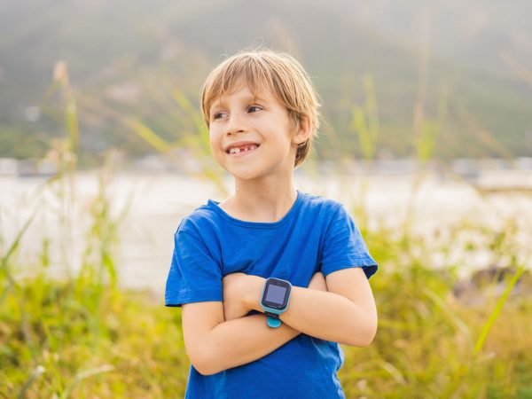 Boy uses kids smart watch outdoor against the background of the garden.