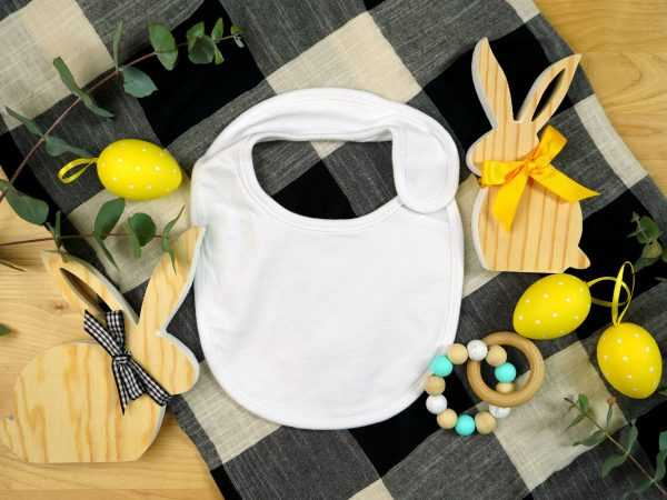 Easter farmhouse theme baby apparel top view flatlay. Baby bib mock up with negative copy space for your text or design here.