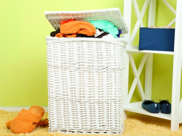 Full laundry basket  on wooden floor on  home interior background