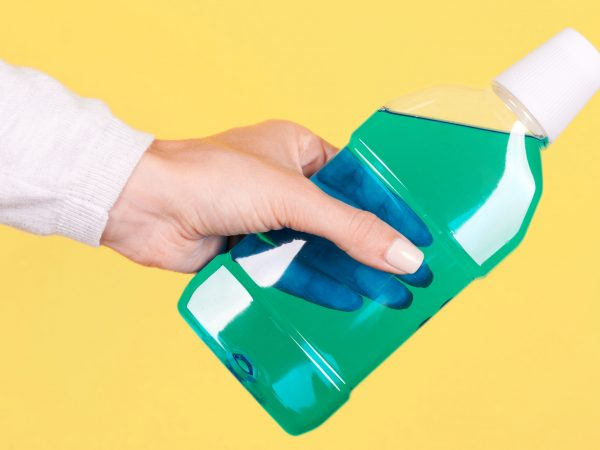 Hand with mouthwash bottle, dental care.