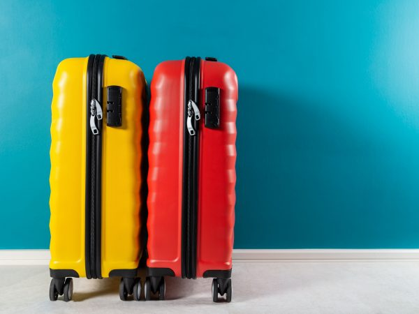 Bright and stylish cabin size suitcases as holiday concept agains dark blue background, copy space. Easy travel with little baggage
