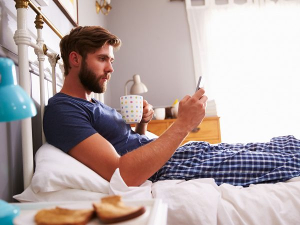 Man Eating Breakfast In Bed Whilst Using Mobile Phone