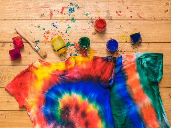 The process of painting a t-shirt in the style of tie dye in the form of a spiral. White clothes painted by hand. Flat lay.