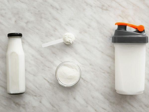 Bottles of protein shake on light background