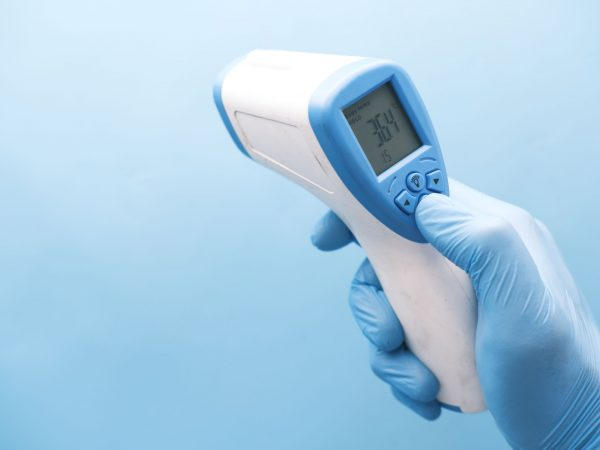 Hand holding infrared thermometer to measuring temperature