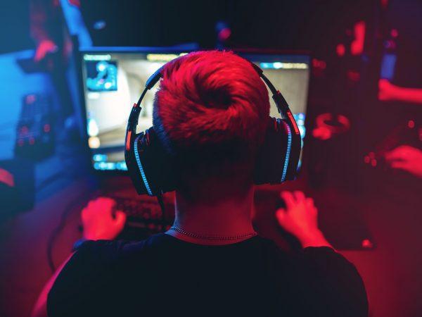 Profesionalus žaidėjas, žaidžiantis internetinių žaidimų turnyrus, kompiuteris su ausinėmis, neryškus raudonas ir mėlynas fonas.