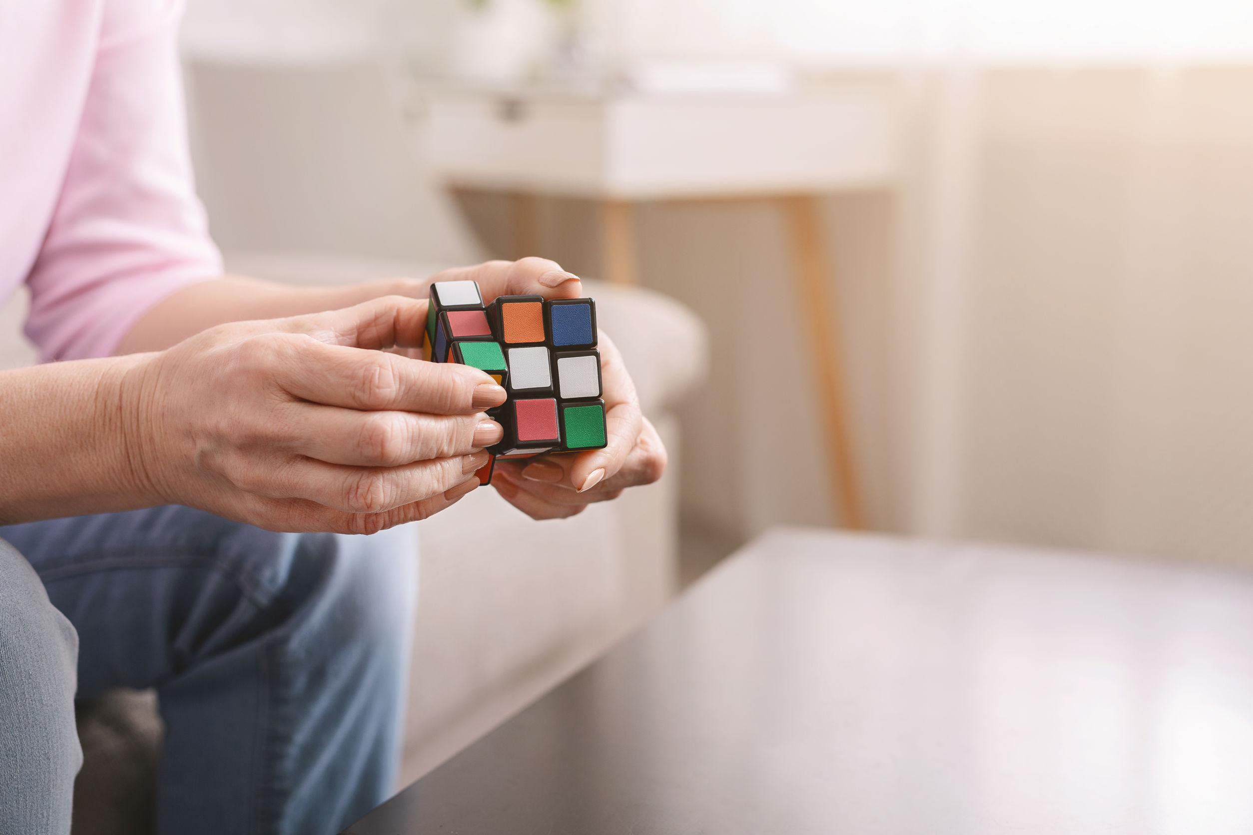 Anciana sosteniendo el cubo de Rubik y jugando con él en casa