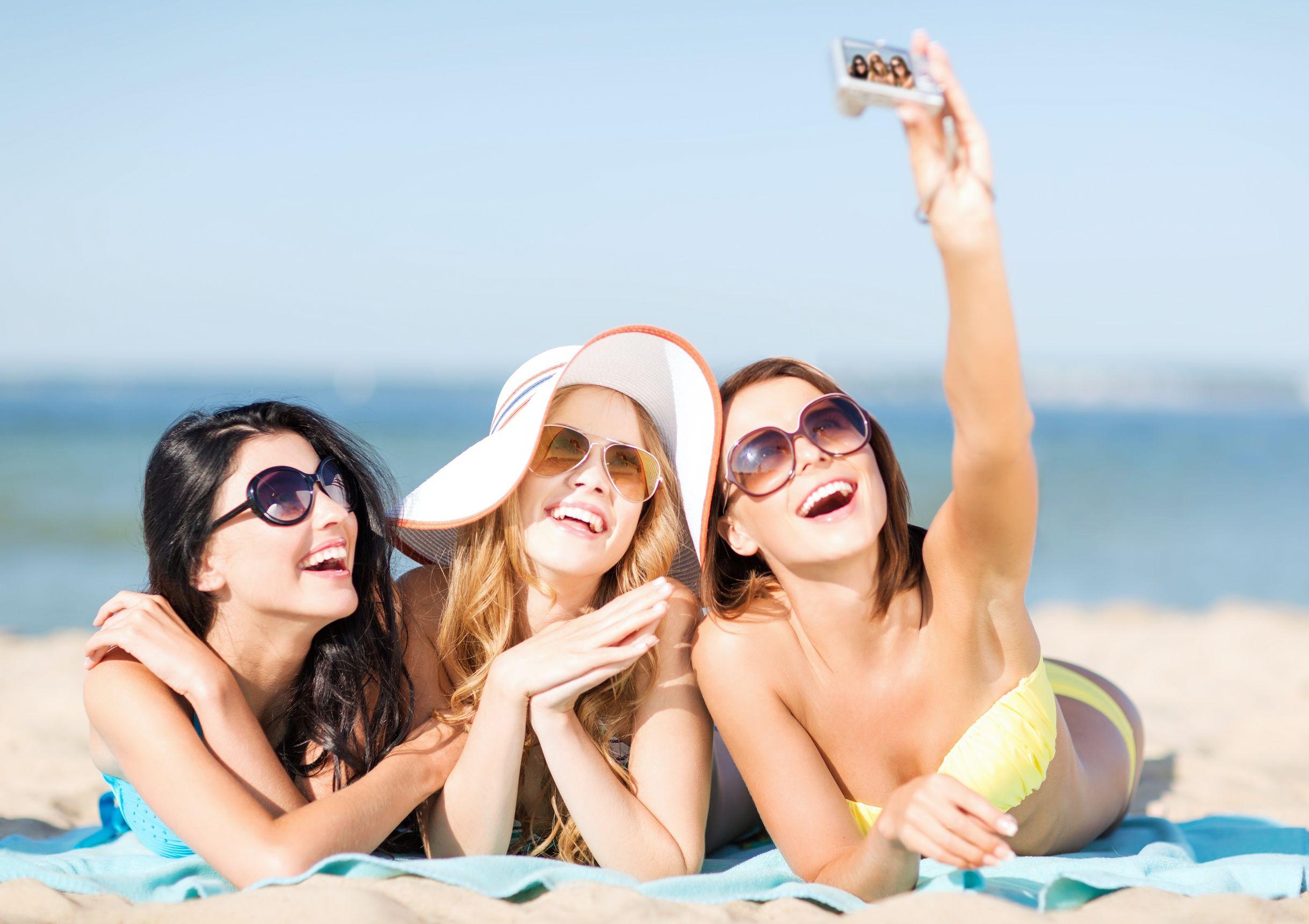 Tres chicas atractivas tomandose una selfie en la playa