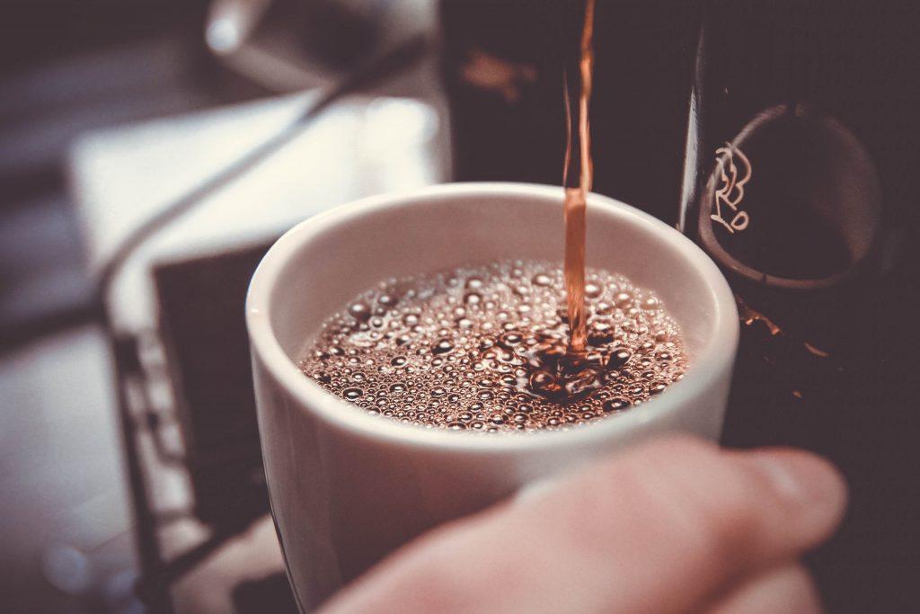 Mano vertiendo café en taza