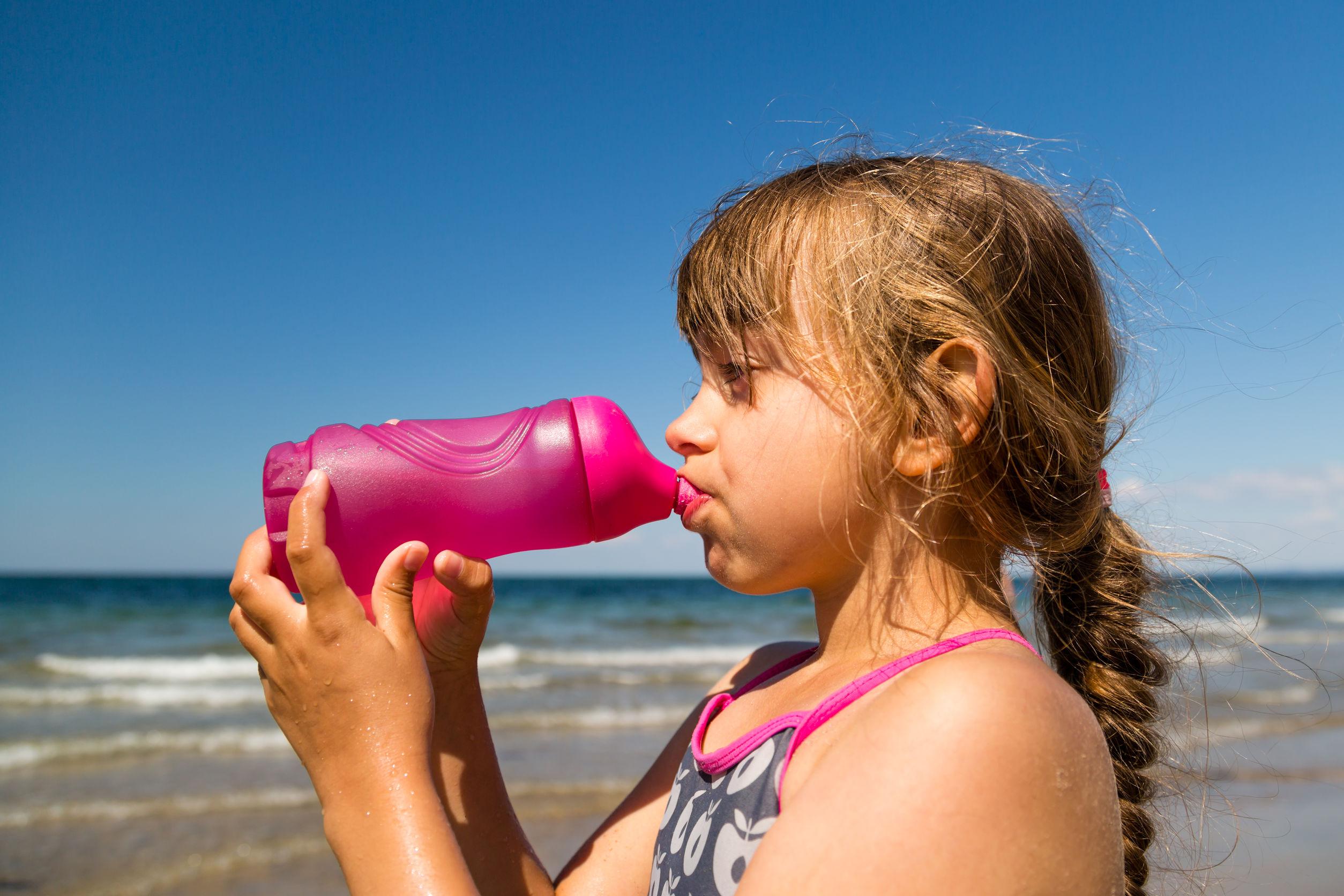 Niña en la playa bebiendo agua de botella