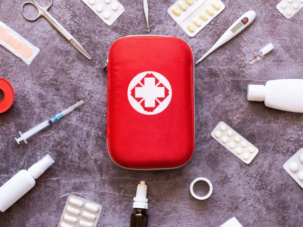 Home first aid kit, pills, thermometer on plain background
