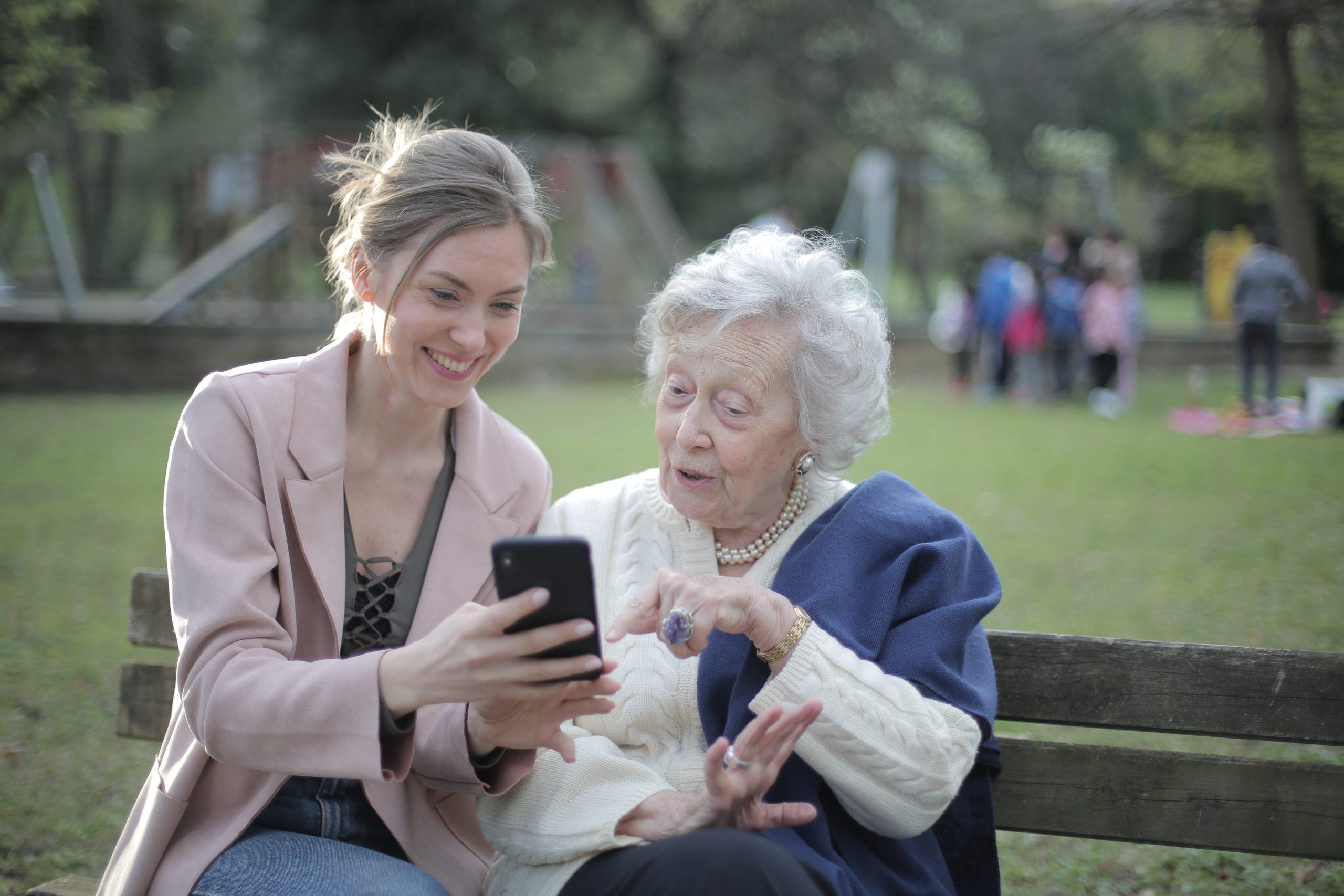 Mujer joven mostrandole smartphone a mujer anciana