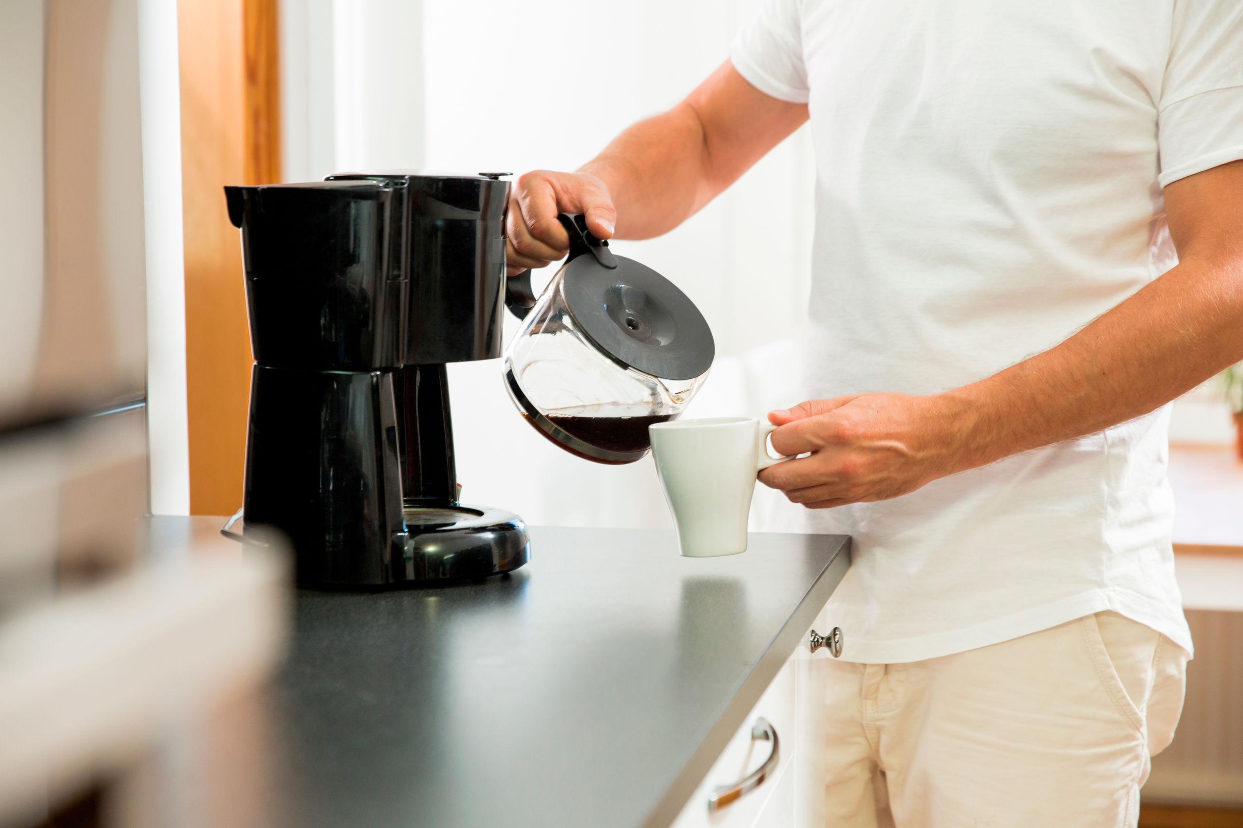 Hombre en la cocina vertiendo una taza de café caliente filtrado de una olla de vidrio