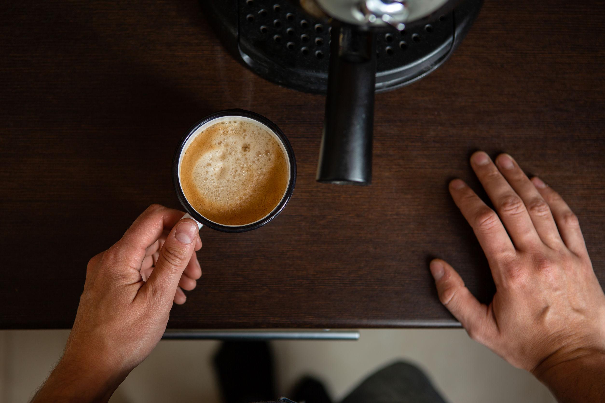 Foto de cafetera, manos del hombre vertiendo café en taza