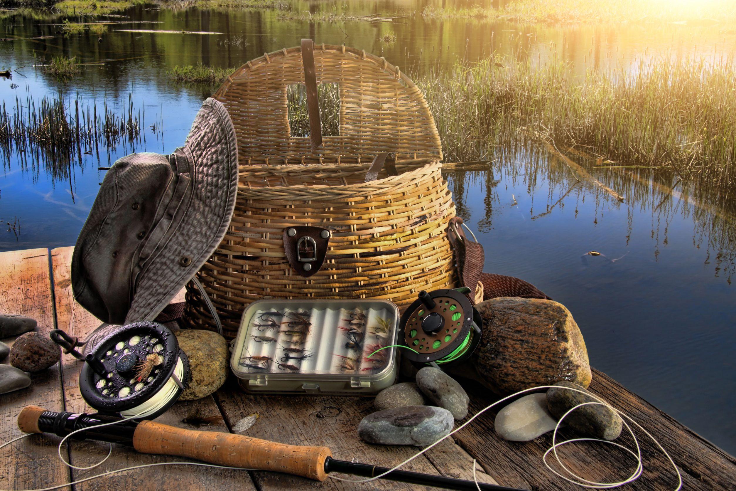 Varilla de tradicionales de pesca con mosca con equipos junto a un lago de final de la tarde
