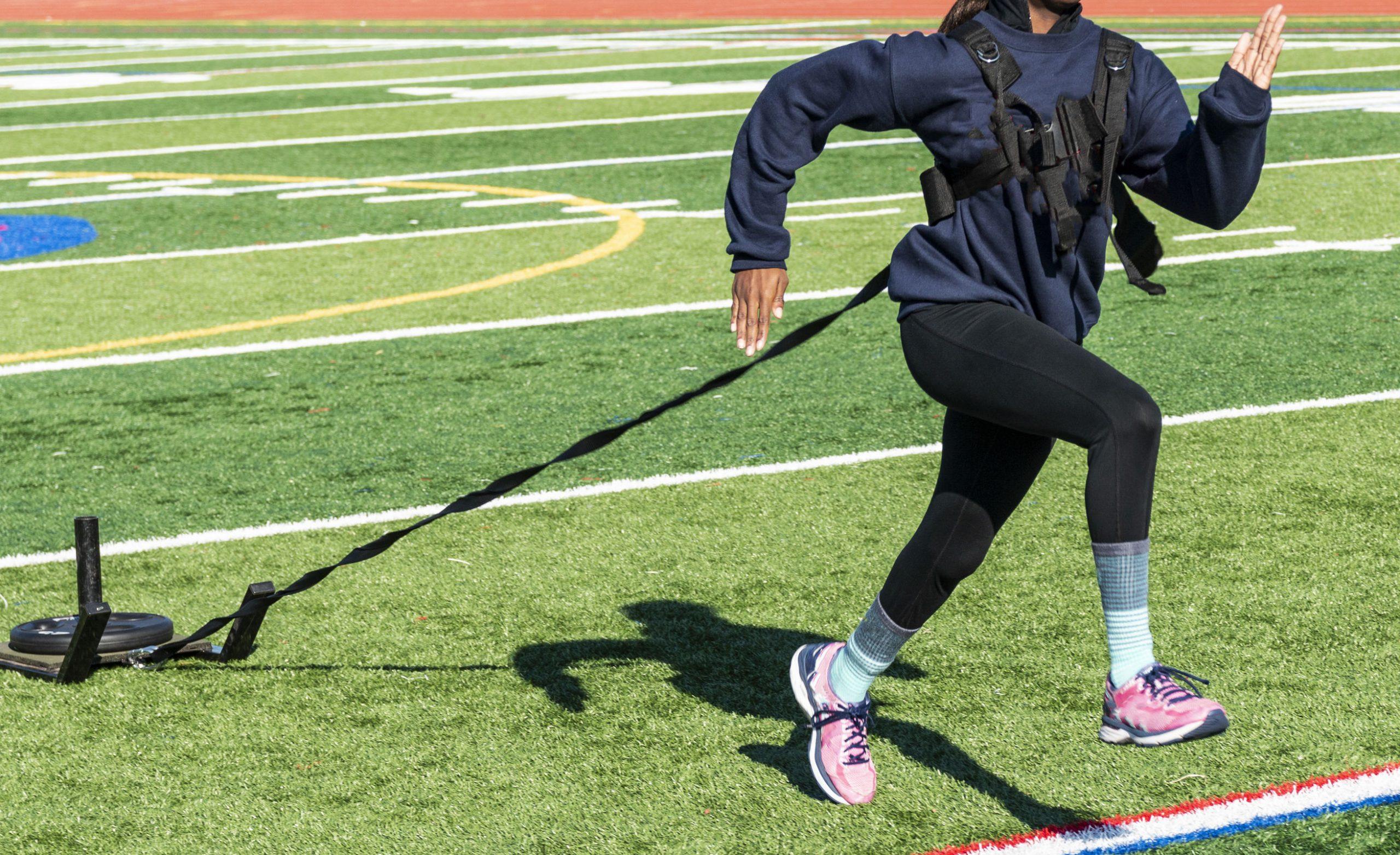 Una velocista de secundaria está corriendo mientras tira de un trineo con un peso sobre él para el entrenamiento de resistencia