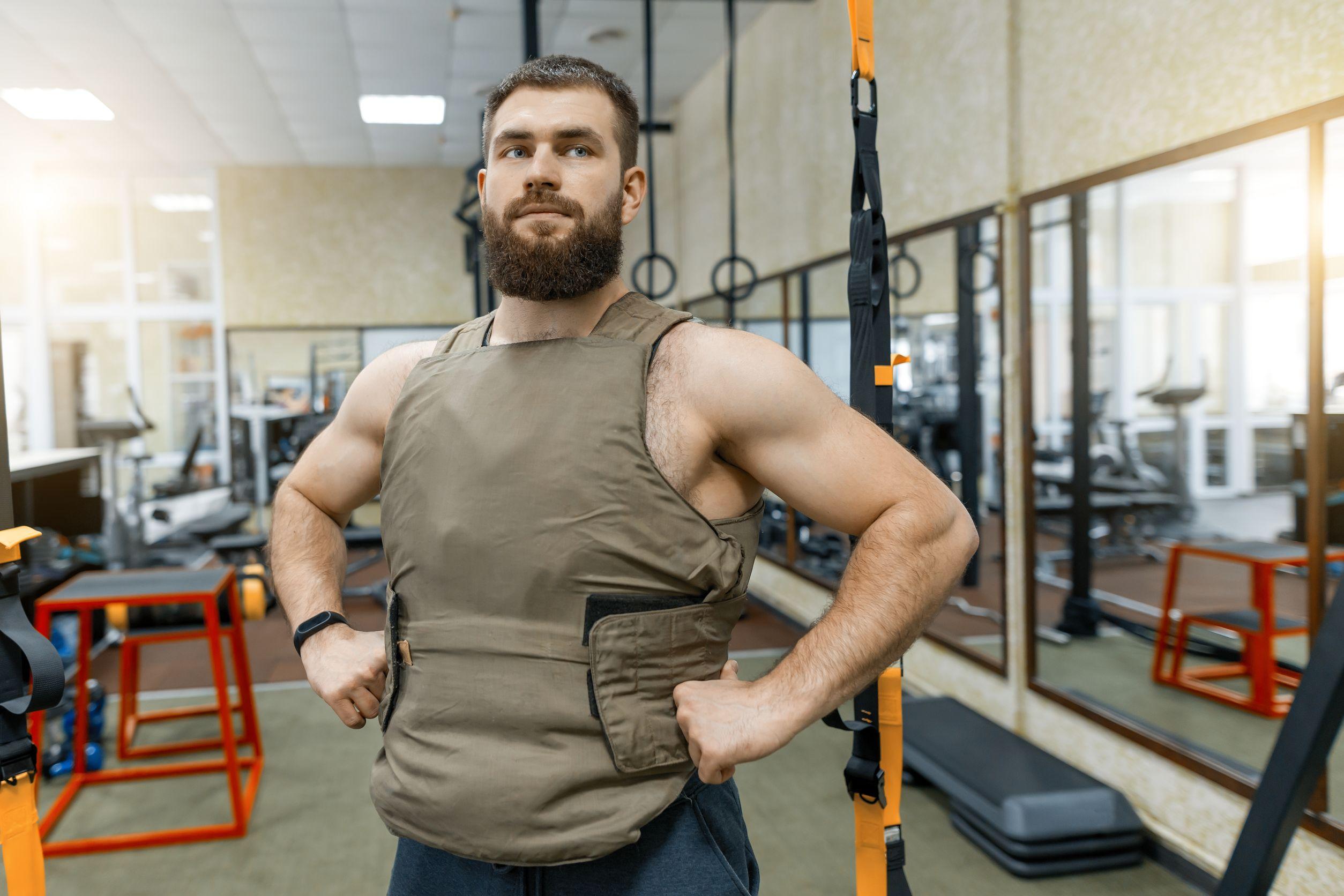 Retrato de hombre barbudo caucásico musculoso vestido con chaleco lastrado en el gimnasio