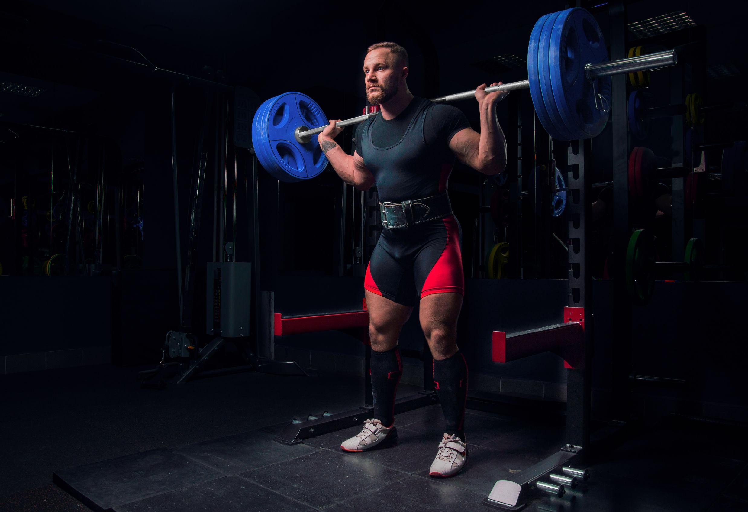 Atleta profesional hace sentadillas con una barra en el gimnasio