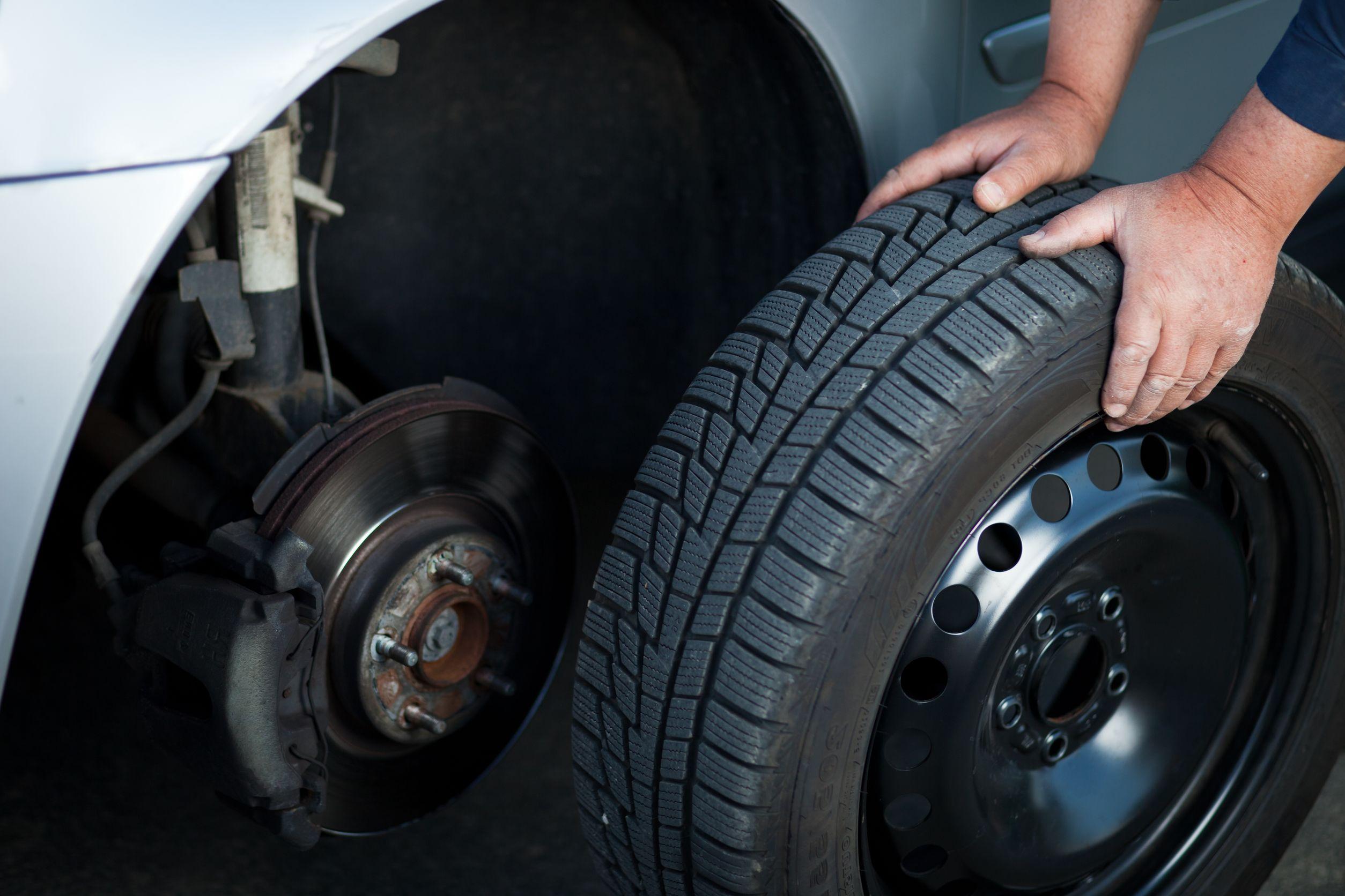 Mecánico de cambiar una rueda de un coche moderno