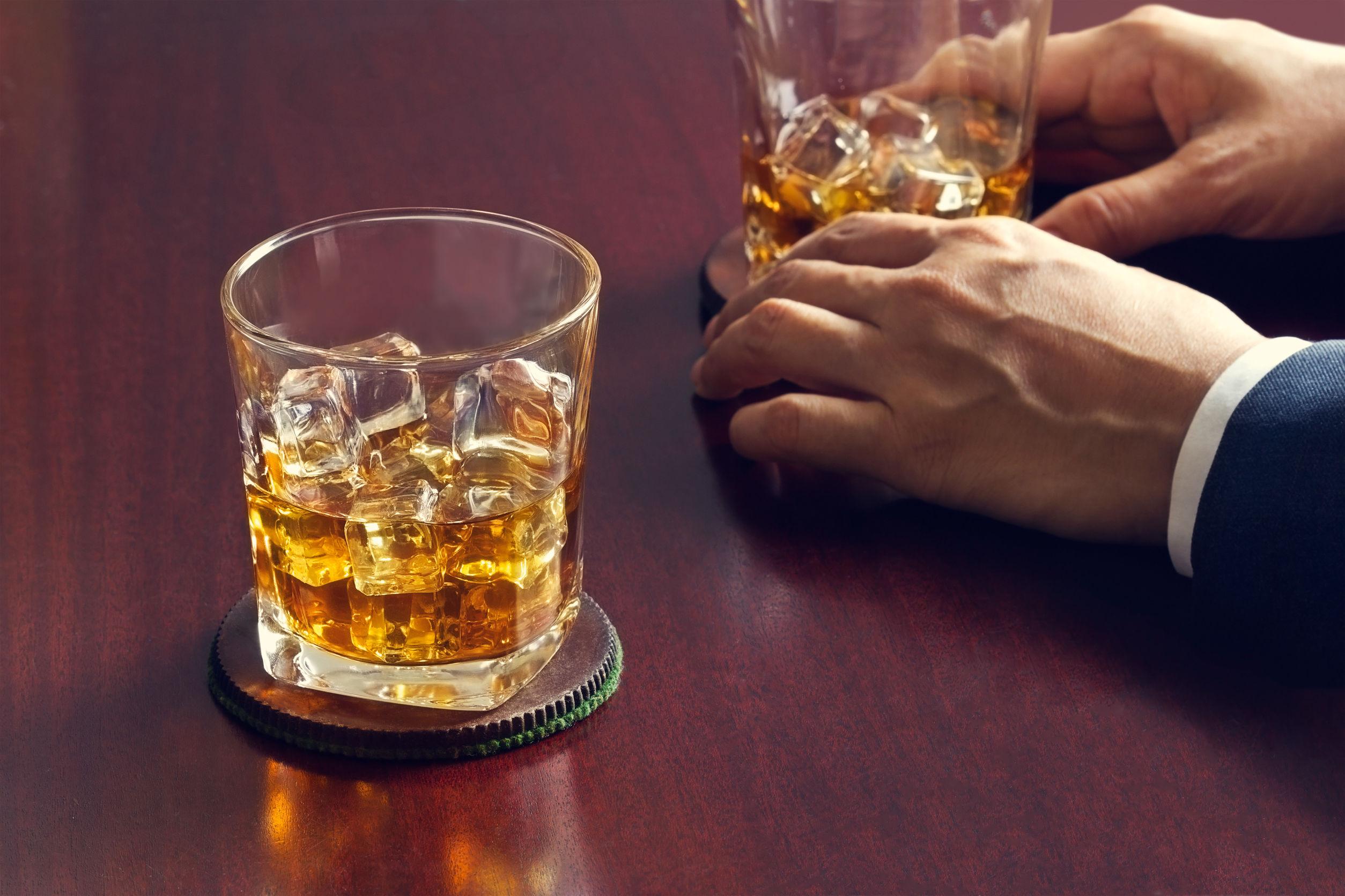 Whisky en la mesa de madera y hombre de negocios con el whisky en la mano