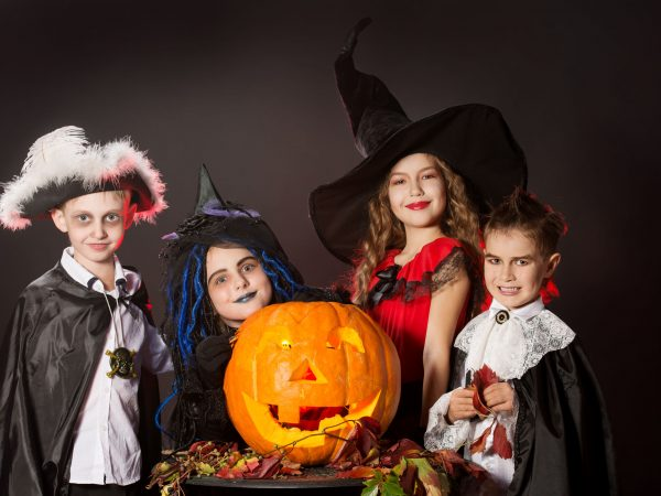 22326583 – cheerful children in halloween costumes posing with pumpkin. over dark background.